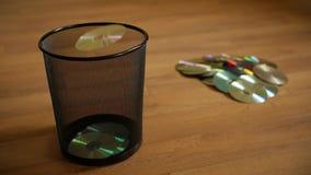 Varios discos digitales inútiles caen en el cubo de basura metrajes