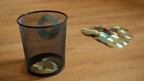 Varios discos digitales inútiles caen en el cubo de basura almacen de video