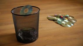 Varios discos digitales inútiles caen en el cubo de basura almacen de metraje de vídeo