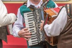 Varios hombres en ropa tradicional juegan el acordeón fotos de archivo