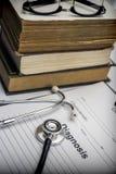 Varios libros médicos con un estetoscopio y una forma de diagnóstico, imágenes de archivo libres de regalías