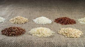 Varios montones del arroz de diversas variedades en el fondo del despido imagen de archivo