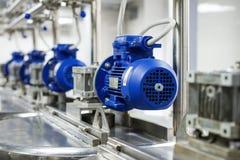 Varios motores eléctricos con los reductores Los tanques para los líquidos de mezcla Fotografía de archivo libre de regalías