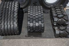 Varios neumáticos de goma negros en venta con diverso modelo de la pisada Fotos de archivo libres de regalías