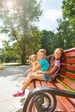Varios niños que se sientan en el banco en verano parquean Foto de archivo libre de regalías