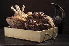 Varios panes del pan en la caja de madera rústica blanca con los oídos del trigo delante del fondo oscuro imagen de archivo