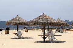 Varios paraguas de la choza de la tienda de los indios norteamericanos fijaron sobre las tablas y las sillas en la playa Imagen de archivo libre de regalías