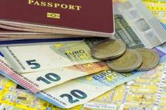 Varios pasaportes y varios billetes de banco euro con las monedas en el fondo del mapa de la ciudad imágenes de archivo libres de regalías