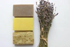 Varios pedazos de jabón hecho a mano y un ramo de flores de la lavanda en un fondo blanco imagen de archivo