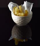Varios pedazos de yuca frita en un cuenco blanco en una superficie negra reflexiva Fotos de archivo