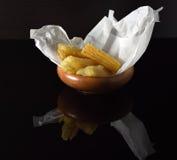 Varios pedazos de yuca frita en un cuenco de madera en una superficie negra reflexiva Foto de archivo