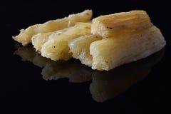 Varios pedazos de yuca frita en una superficie negra reflexiva Fotografía de archivo