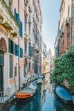 Varios pequeños barcos azules atados a una casa con una pared de ladrillo en un canal estrecho con una reflexión hermosa, Venecia Fotografía de archivo