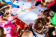 Varios pequeños niños dibujan en una hoja de papel con los lápices Una visión desde arriba Imágenes de archivo libres de regalías