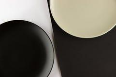 Varios placas llanos y tazas en fondo blanco y negro Fotos de archivo libres de regalías