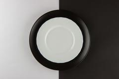 Varios placas llanos y tazas en fondo blanco y negro Foto de archivo libre de regalías