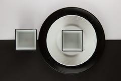 Varios placas llanos y tazas en fondo blanco y negro Imagenes de archivo