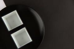 Varios placas llanos y tazas en fondo blanco y negro Fotos de archivo