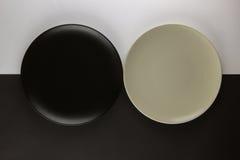 Varios placas llanos y tazas en fondo blanco y negro Imagen de archivo libre de regalías