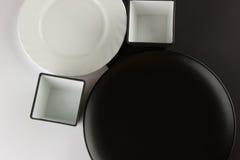 Varios placas llanos y tazas en fondo blanco y negro Imagen de archivo