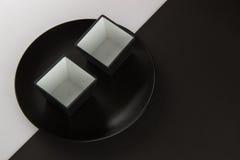 Varios placas llanos y tazas en fondo blanco y negro Fotografía de archivo libre de regalías
