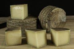 Varios quesos de Manchego, uno de ellos cutted en pedazos Fotografía de archivo
