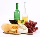 Varios tipos de queso, de vino, de uvas y de galletas Foto de archivo