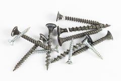 Varios tornillos usados de diverso tipo en el fondo blanco Foto de archivo