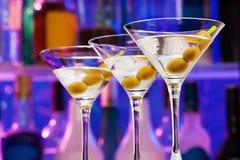 Varios vidrios de cóctel con las aceitunas en la barra Foto de archivo libre de regalías