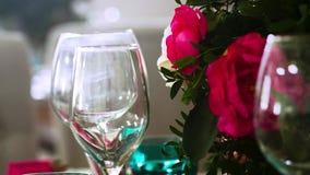 Varios vidrios para el vino rodeado por los vidrios y las placas y el centro de flores almacen de video