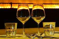 Varios vidrios y vajilla en el oro negro un fondo con reflexiones hermosas Fotografía de archivo
