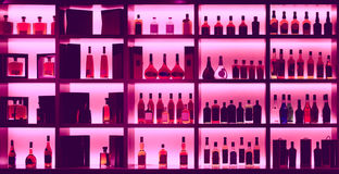 Various alcohol bottles in a bar, back light, logos removed, ton Stock Image