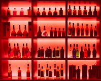 Various alcohol bottles in a bar, back light, logos removed, ton Royalty Free Stock Image
