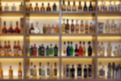 Various alcohol bottles in bar, strong blur Stock Images