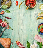 Various antipasti with ciabatta bread, pesto and ham on rustic wooden background, top view, frame. Royalty Free Stock Photography