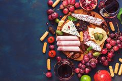 Various appetizer-red wine, fruits,sausages,cheese, vegetables on a dark finem background. Copy space, top view. stock images