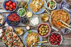 Various Asian and European snacks at dinner table, top view. The concept: the abundance of products. Wooden background Royalty Free Stock Photo