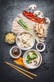 Various Asian vegetarian cooking ingredients and chopsticks with tofu, noodles, ginger, cut vegetables, Sprout,green onion ,hoisin. And austern sauce on dark royalty free stock image
