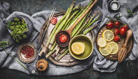 Various asparagus ingredients on rustic kitchen table background with bowls and tools, top view. Dark. Style Stock Image