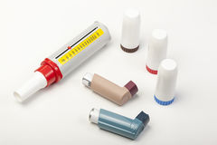 Various asthma inhalers and a peek low meter on white Royalty Free Stock Photos