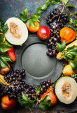 Various autumn harvest fruits and vegetables atound blank vintage dish, top view Stock Photos