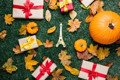 Various autumn leaves and orange pumpkins near Eiffel tower toy Royalty Free Stock Photography