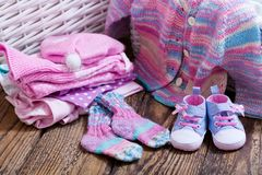 Baby clothes on wooden table. Various baby clothes on wooden table royalty free stock image