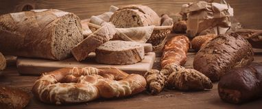 Various baked breads and rolls on rustic wooden table. Close up Stock Photos
