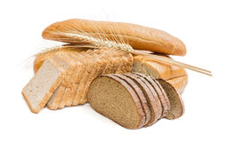 Various bakery products and wheat spikelets on a light backgroun Stock Photos