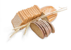 Various bakery products and wheat spikelets on a light backgroun Royalty Free Stock Images