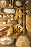 Various bakery on wheat background. Various types of bakery with wooden spoons on wheat background Stock Images