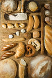Various bakery on wheat background. Various types of bakery with wooden spoons on wheat background Royalty Free Stock Images