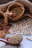 Various bean cultures. Close-up of various of bean cultures on table in textile brown bag Royalty Free Stock Photo