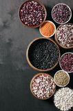 Various beans in bowls. Set of various beans in bowls: white, black, purple and red speckled beans, red and green lentils. Black wooden background, top view Stock Photography